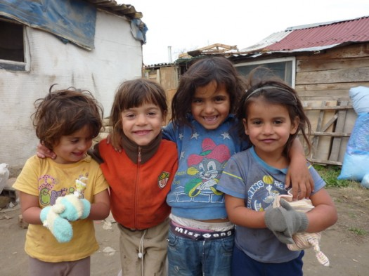 Happy children showing off the gloves they received as part of the aid delivery.
