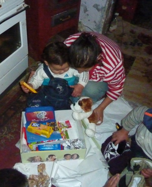 """Roma child opening his Christmas """"shoe box"""" gift package."""